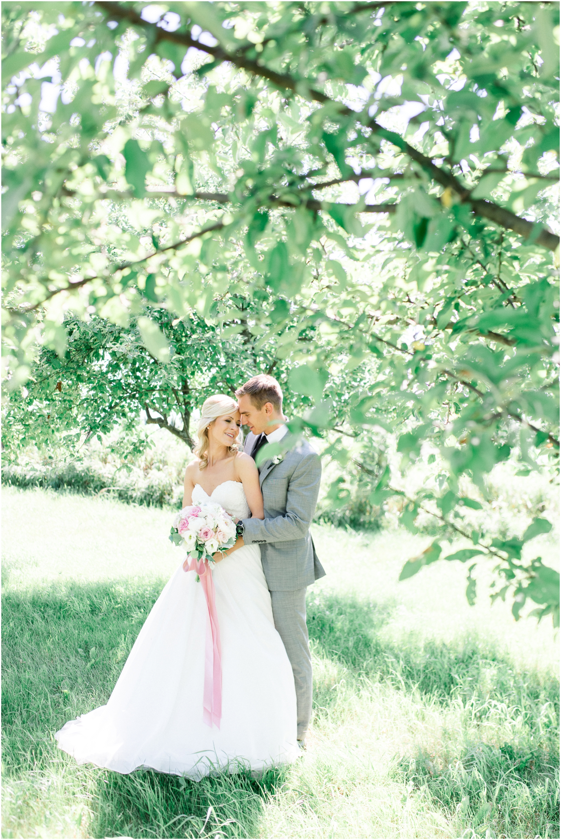 bride and groom embracing in apple orchard