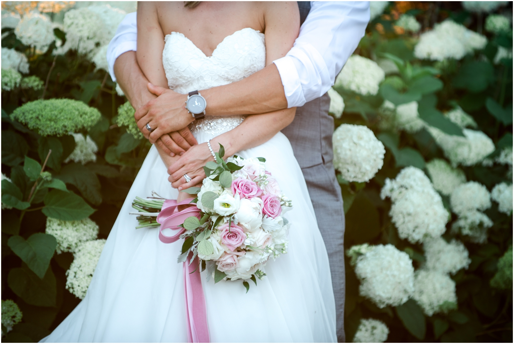 bride and groom's hands holding flowers