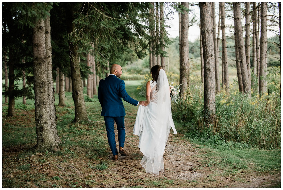 Elegant bride and groom on wedding day, holding hands and walking through the woods at Royal Ashburn venue in Whitby