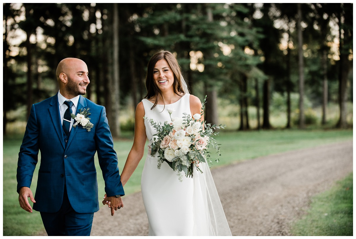 Stunning wedding portrait of elegant bride and groom holding hands at Royal Ashburn in Whitby