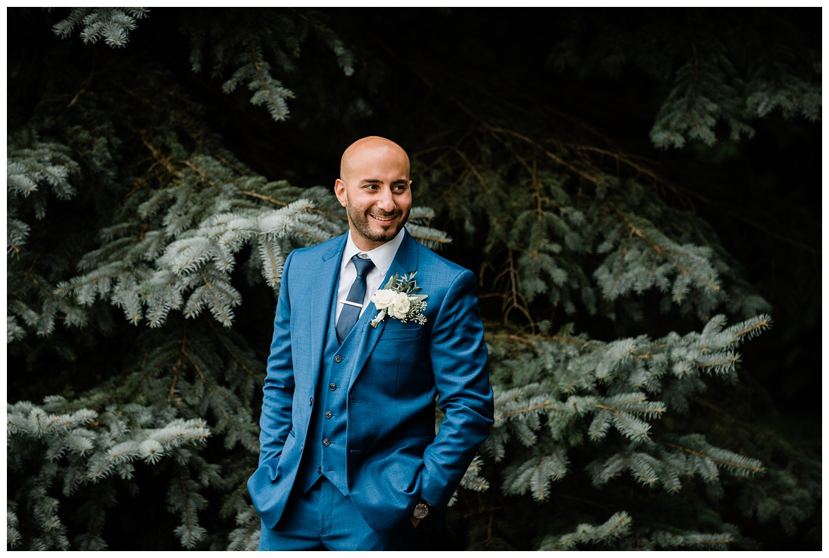 Portrait of handsome groom in blue suit at Royal Ashburn wedding in Whitby