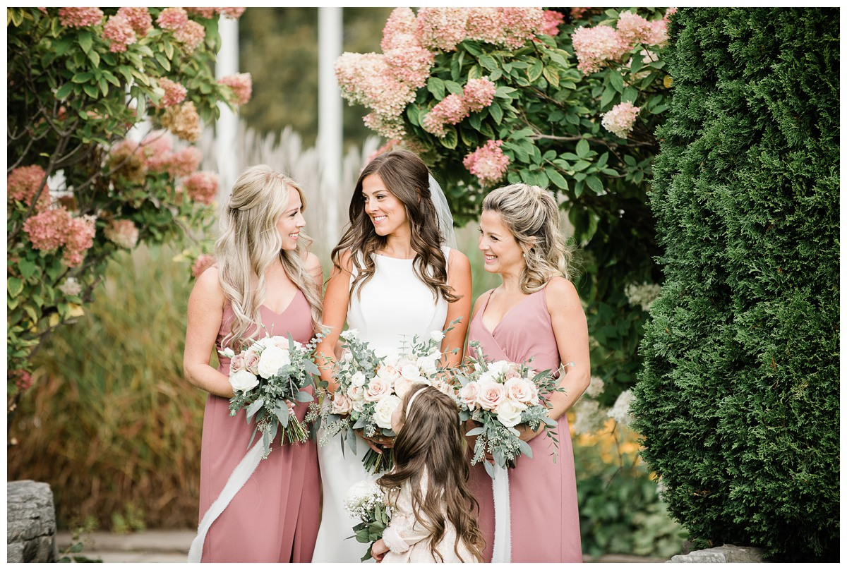 Elegant bride and her blush bridesmaids laughing on wedding day at Royal Ashburn in Whitby