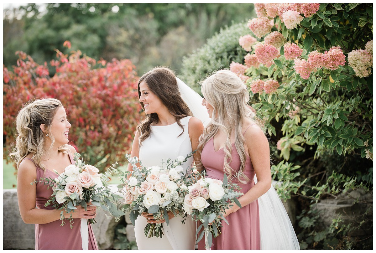 Stunning bride and dusty rose bridesmaids laughing at Royal Ashburn wedding in Whitby