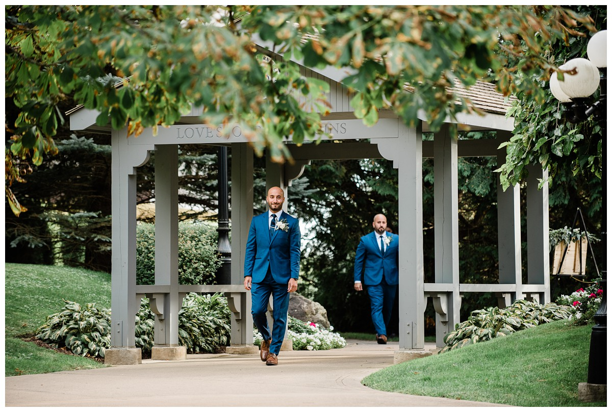 Handsome groom in chic blue suit walks down the aisle at Royal Ashburn wedding in Whitby