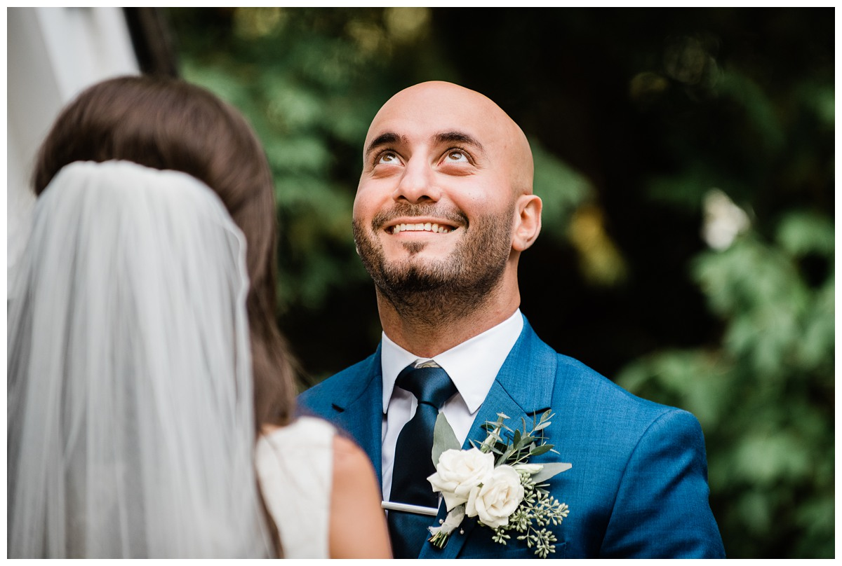 Handsome groom in blue suit gets emotional after seeing bride for first time at wedding alter at Royal Ashburn in Whitby