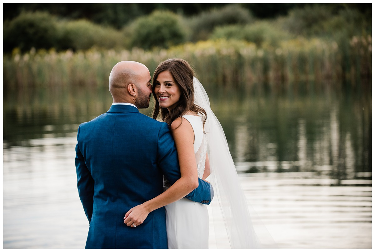 Elegant bride and groom by a pond on wedding day at Royal Ashburn in Whitby
