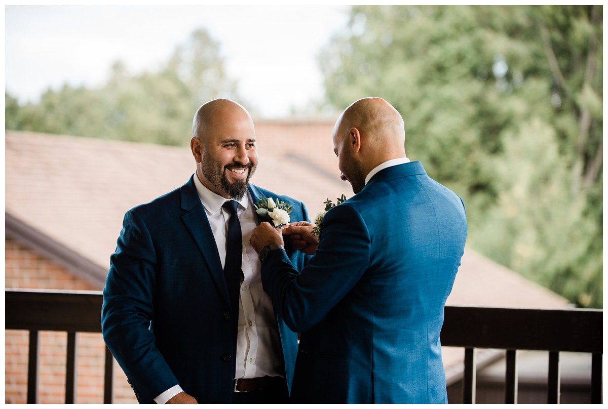 Handsome groom attaching boutonnière at elegant wedding at Royal Ashburn in Whitby