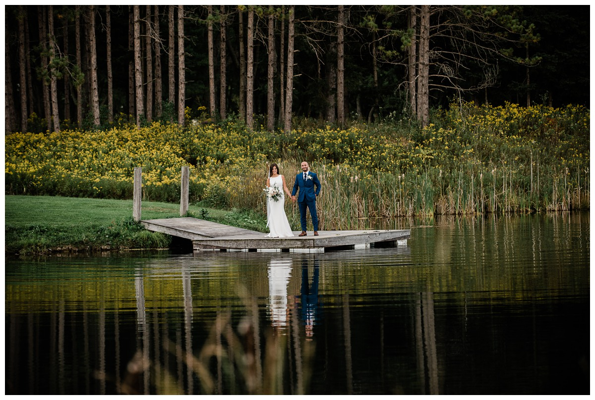 Reflection of elegant bride and groom holding hands by a pond at Royal Ashburn wedding in Whitby